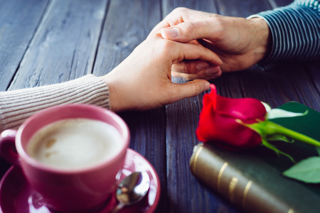 Romantic lovers dating  Male and female hands caressing with love  Couple on secret dating at coffee shop