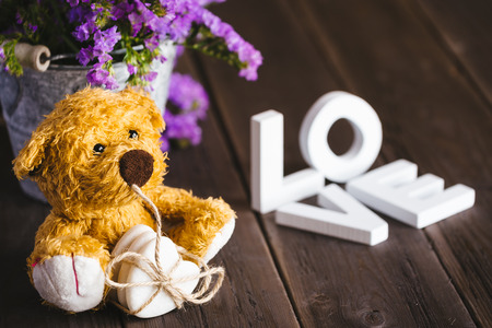 Cute love words and lovely teddy bear on rustic wooden table