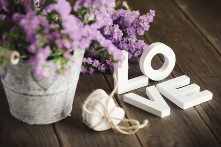 Cute love words and beautiful flowers on rustic wooden table  Фото со стока