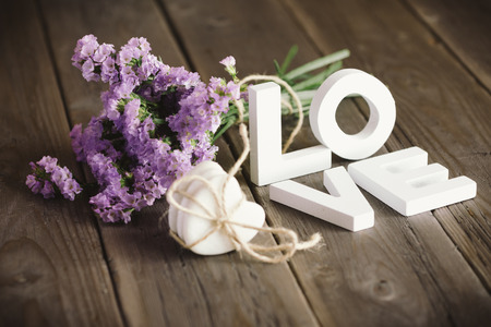 Cute love words and beautiful delicate flowers on rustic wooden table