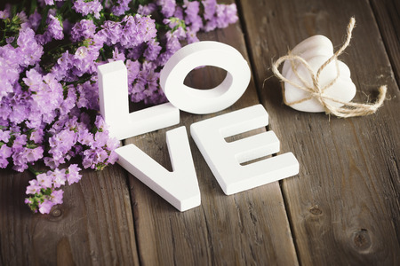 Cute love words, hearts and beautiful delicate flowers on rustic wooden table  photo