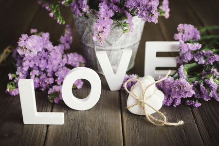Cute love words, stone little hearts and beautiful delicate flowers on rustic wooden table