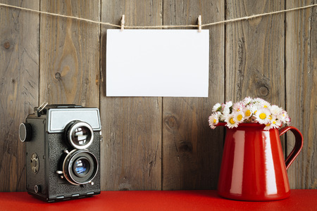 Blank instant photo hanging on rope with retro camera and lovely daisies on red flower pot on rustic wooden wall