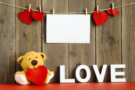 Blank instant photo hanging on rope with lovely hearts, cute teddy bear with the word love on rustic wooden wall