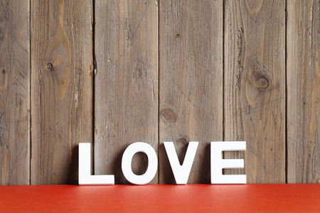 Love concept background   White letters over red table on rustic wooden wall  Фото со стока