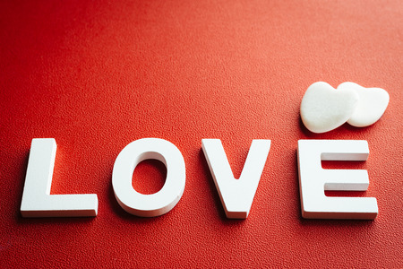 Love concept background   White letters on red texturated table with little stone hearts