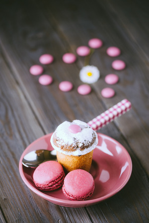 Lovely sweet dessert with small almond cake, pink raspberry french macaroons and candies on rustic wooden table