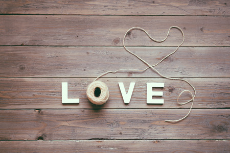 Love instagram filtered concept background   Heart shaped rustic rope or string on wooden table