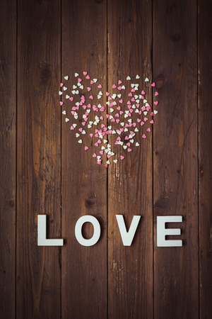 Instagram filtered love concept background with pink and white sugar candy hearts and letters on rustic old wooden wall  Фото со стока