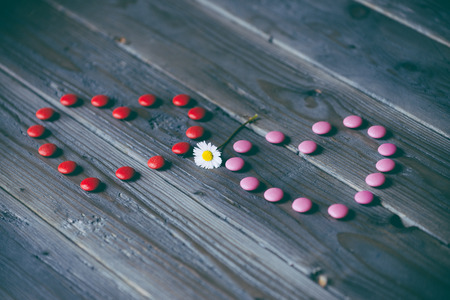 Love concept with red and pink candy hearts and little flower  Instagram filtered cute background