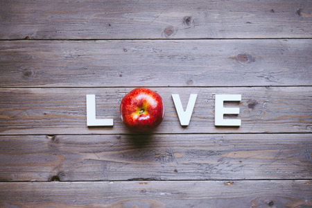 Love instagram filtered concept background with red apple and letters on rustic wooden table