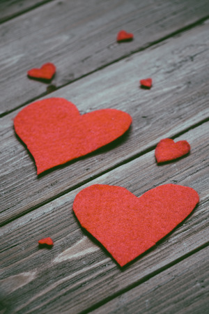 Love instagram filtered concept background with red little felt hearts on rustic wooden table