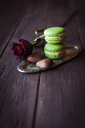 Sweet little green macaroons on old silver platter and rose  Vintage instagram filtered food french confectionery