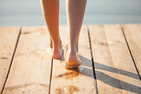 Human Wet footprints on the bright wooden plank floor. Walk from beach to hotel or home. Abstract backgrounds and wallpapers. Holidays and vacations in summer.
