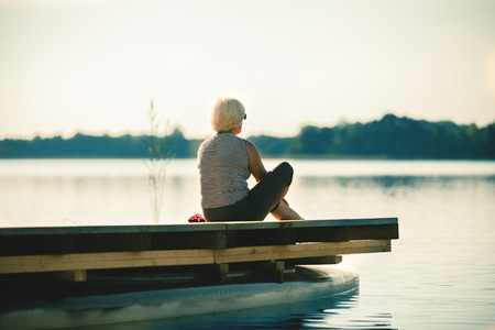 woman sunset: Senior woman sitting by the lake Stock Photo