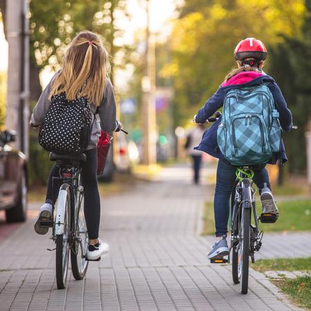 二人の女の子が自転車に乗って