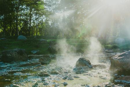El vapor y el aumento de azufre a partir de una fuente termal de colores en la superficie de la tierra