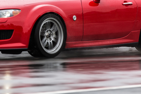 torrential: Sports car driven on rainy roads close up on a wheel with motion blur effect