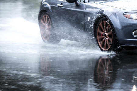 Sports car driven on rainy roads close up on a wheel with motion blur effect 版權商用圖片 - 81285473