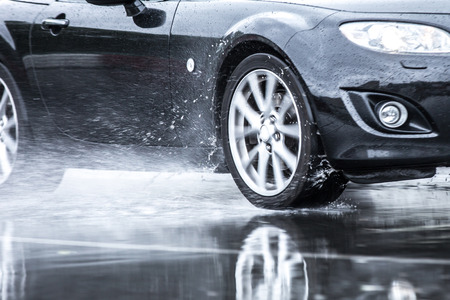 Sports car driven on rainy roads close up on a wheel with motion blur effect