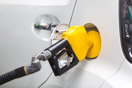 White car being filled with fuel at the gas station Stock Photo