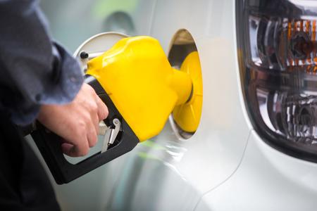 주유소에서 연료로 채워지는 하얀 차 스톡 콘텐츠