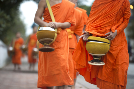 Buddhist monks on a traditional morning alms giving in Luang Prabang, Laos. Stock Photo