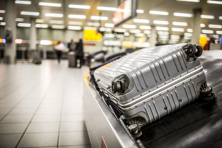 Wheeled suitcase on a luggage belt at the airport terminal. Фото со стока