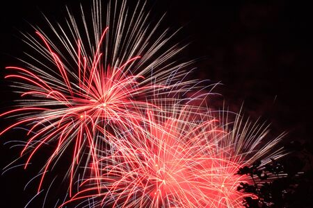 Beautiful colorful fireworks in the night sky, fireworks in the night sky. Decoration for Christmas, New Year, Valentine Day celebration, holiday.