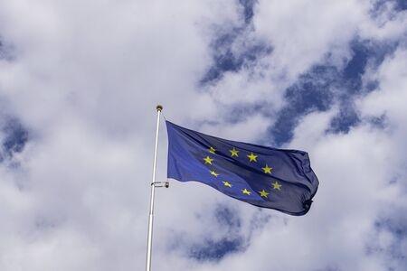 European Union flag waving, with clouds background
