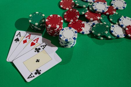 Four aces and poker chips on green surface with afternoon sunlight Stock Photo