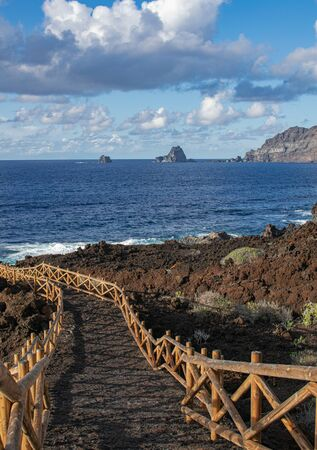 Sentier volcanique avec balustrade en bois, avec Roques de Salmor, océan Atlantique, fond de ciel bleu et nuages, à Charco de los Sargos, Frontera, île d'El Hierro, îles Canaries, Espagne Banque d'images