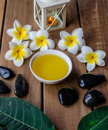 Massage oil with plumeria flowers and leaves, orange candle, black round stones on wooden surface Stock Photo