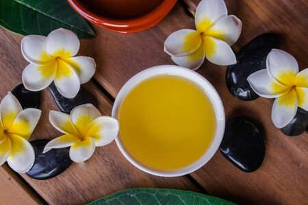Massage oil with plumeria flowers and leaves, black round stones, on wooden surface Фото со стока