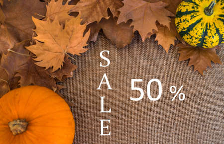 50% sale text, on sack surface with autumn dry leaves and pumpkins