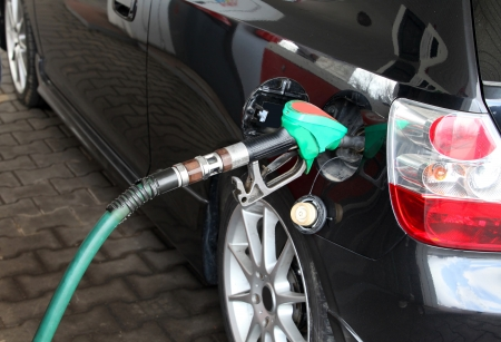 fueling: Male Hand Refilling the black Car with Fuel on a Filling Station