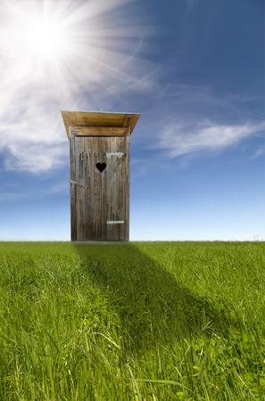 privy: Wooden toilet, green field, blue sky