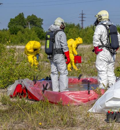 Leden Hazmat team zijn het dragen van beschermende kleding om hen te beschermen tegen gevaarlijke stoffen Stockfoto