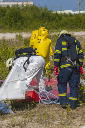 self contained:  Hazmat team members have been wearing protective suits to protect them from hazardous materials Stock Photo