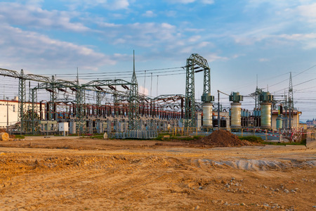 isolator switch: High voltage power transformer substation, field, blue sky Stock Photo