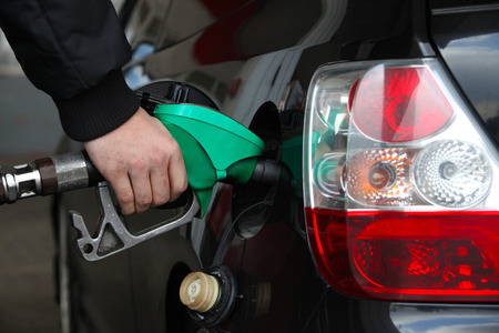 refilling: Male Hand Refilling the black Car with Fuel on a Filling Station