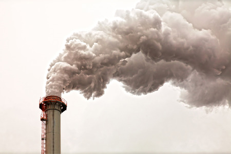 high industrial: Closeup of dirty dark smoke clouds from a high industrial chimney Stock Photo