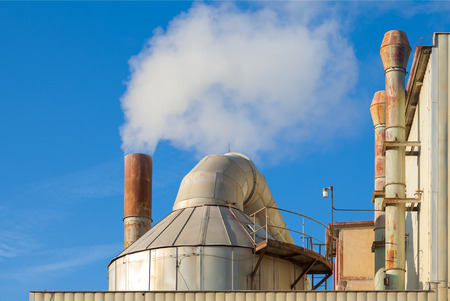 co2 emissions: Smoking chimneys of a factory against a blue sky