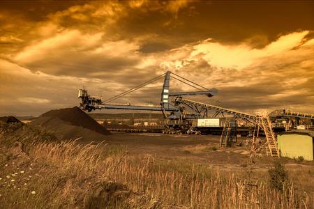carbone: Un escavatore gommato gigante nella miniera di carbone marrone al tramonto