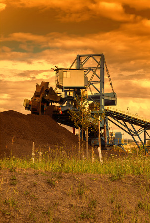 geologists: A giant wheel excavator in brown coal mine at sunset