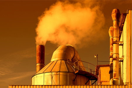 pollutants: Smoking chimneys of a factory in the sunset