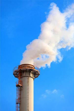 carbon emission: Dense smoke from a chimney, blue sky