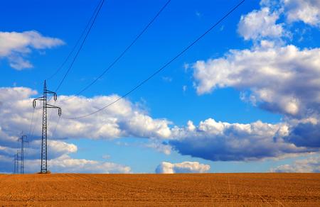 energia electrica: Líneas eléctricas que se ejecutan a través de un campo de trigo con cielo azul