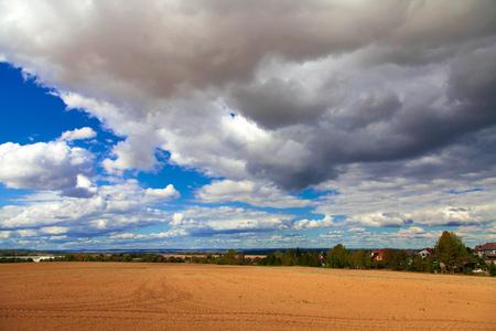 plowed field: Plowed field, cloudy sky