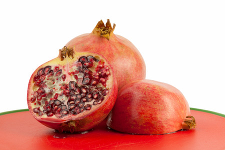grenadine: Ripe pomegranate isolated on red chopping board Stock Photo